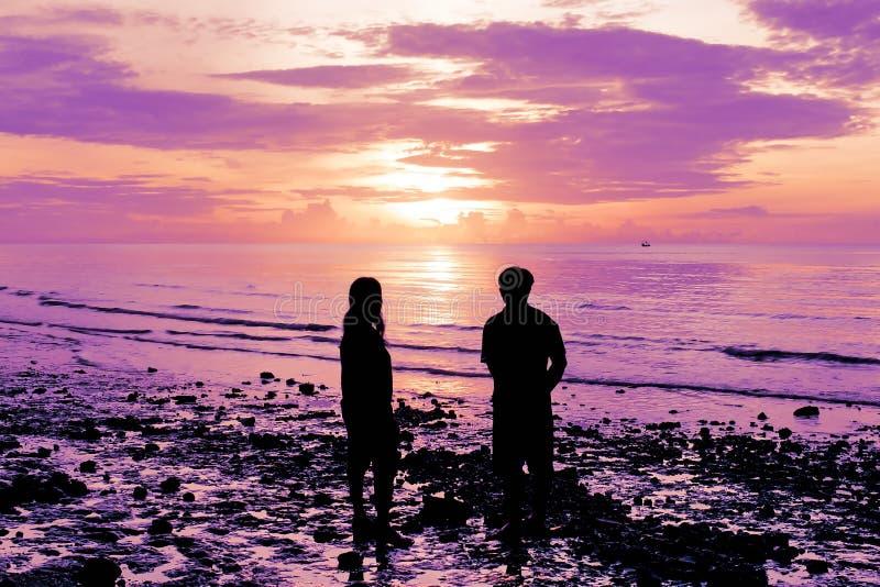 Las sombras de hombres y de mujeres están mirando el sol el subir en la playa imagen de archivo libre de regalías