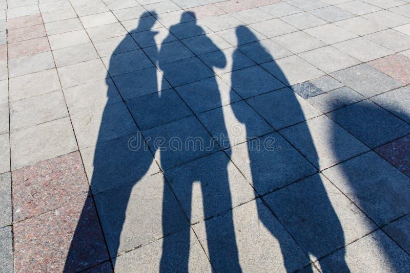 Las sombras de tres personas en las tejas de un pavimento imágenes de archivo libres de regalías