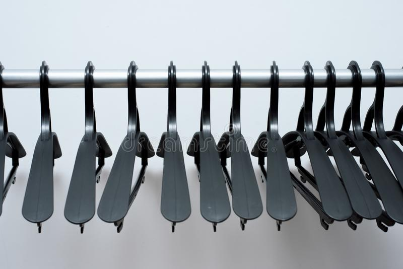 Las suspensiones plásticas negras cuelgan en un fondo ligero muchas diversas suspensiones Estante de la capa del piso foto de archivo libre de regalías