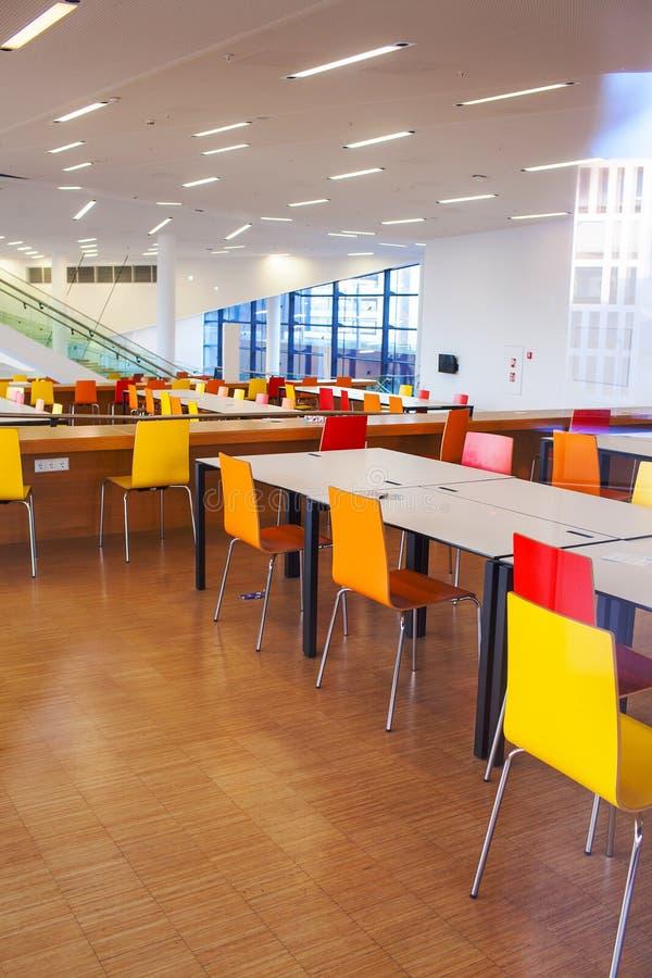 Las tablas con las sillas se colocan en la sala de clase fotos de archivo