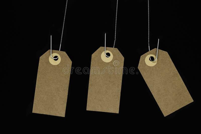 Las tarjetas de nota marrones en blanco colgantes con el espacio de la copia enganchado en el metal saltan y aislaron en fondo ne fotografía de archivo