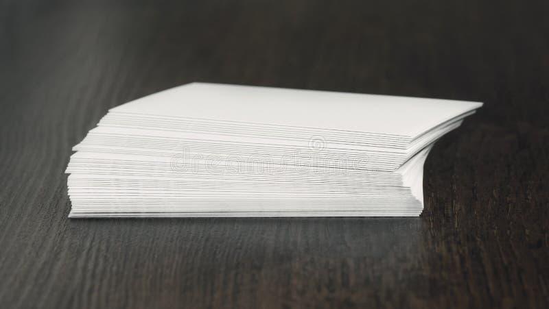 Las tarjetas de visita esconden blanco en una tabla de madera, fotos de archivo