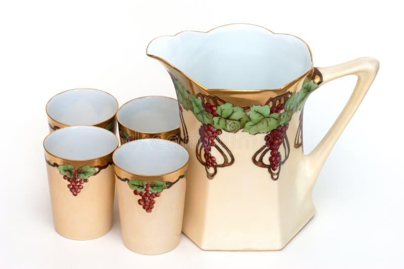 Las tazas antiguas de la jarra fijaron el jugo de uva pintado a mano imagen de archivo