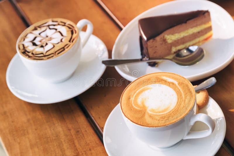 Las tazas de café y de mousse de chocolate calientes del capuchino se apelmazan imagen de archivo libre de regalías