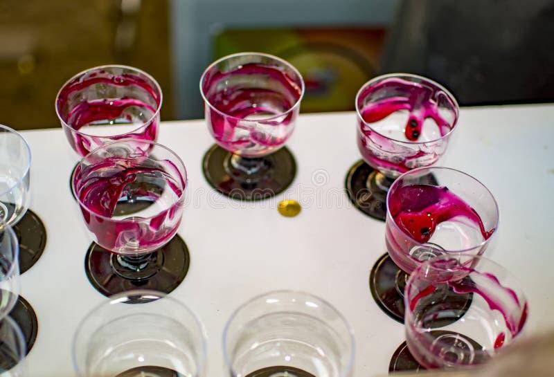Las tazas y los vidrios llenaron del jarabe de fresa rojo fotos de archivo