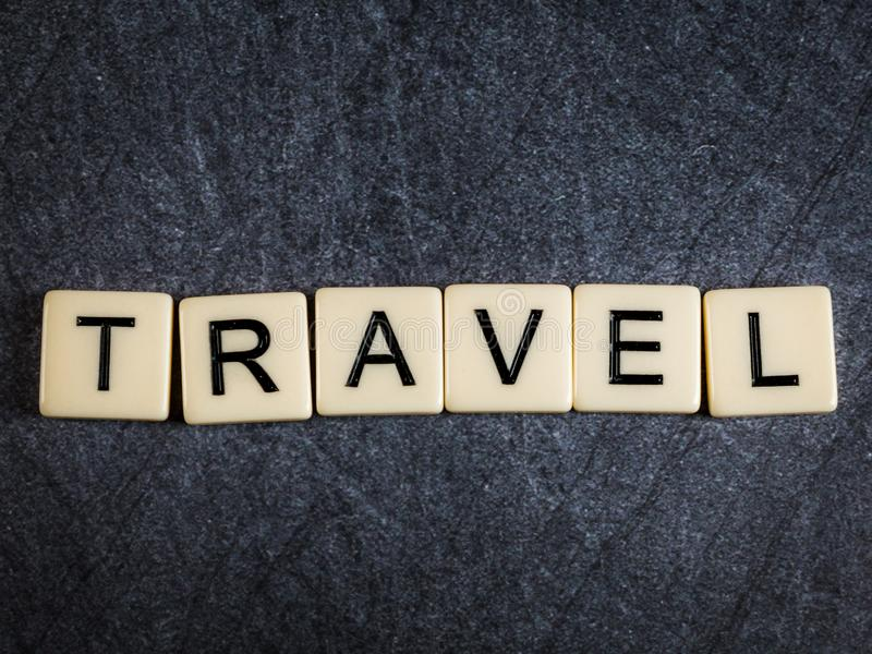 Las tejas de la letra en el deletreo negro del fondo de la pizarra viajan foto de archivo