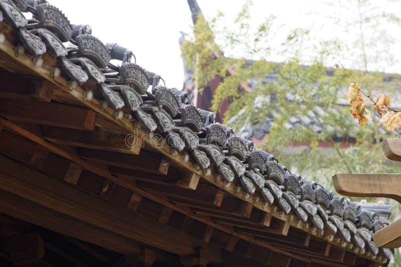 Las tejas negras cubren el pasillo arbolado del tejado-Lleno imagen de archivo