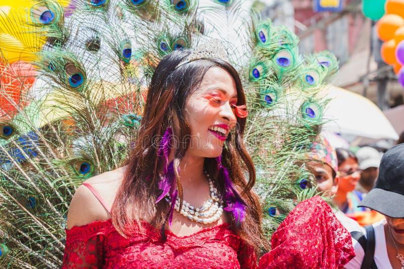 Las terceras mujeres de los géneros con el pavo real empluman en el festival de Gaijatra adentro fotografía de archivo libre de regalías