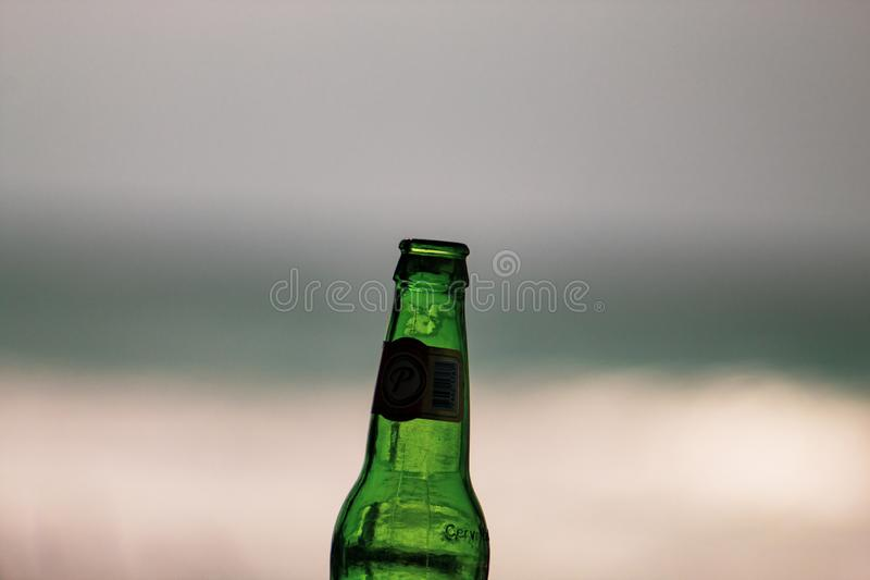 Las Terrenas, Dominican Republic, 6 april, 2019 / A bottle of famous, local Cerveza Presidente beer on the beach. iconc image royalty free stock photography