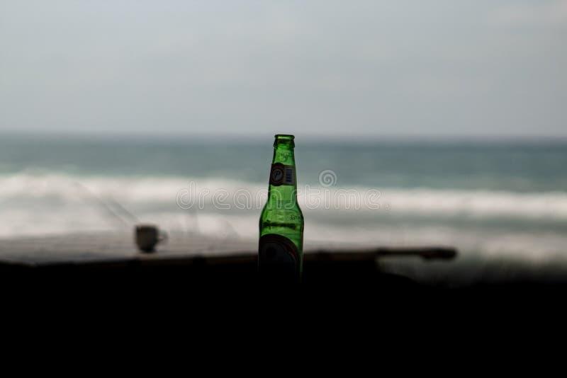 Las Terrenas, Dominikanische Republik, am 6. April 2019/eine Flasche ber?hmtes, lokales Bier Cerveza Presidente auf dem Strand ic stockfotografie