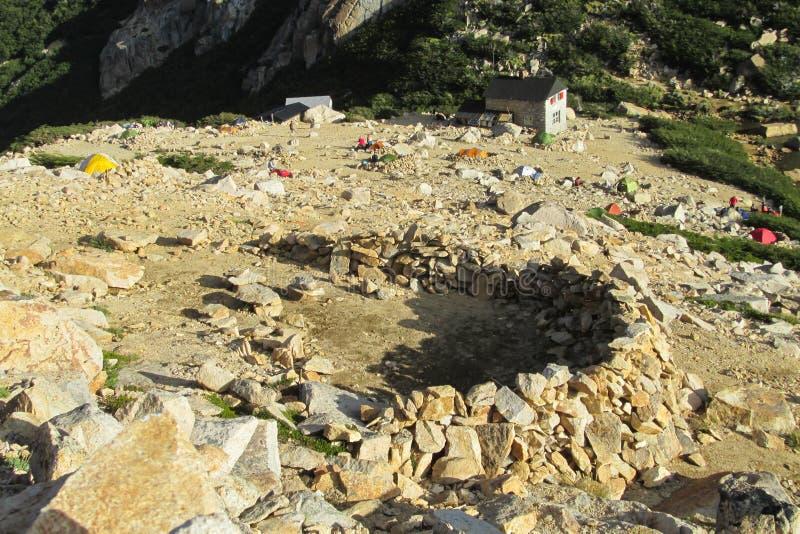 Las tiendas en las rocas acercan al refugio de la montaña imagenes de archivo