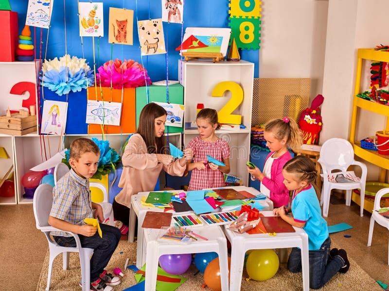 Las tijeras preescolares en niños dan el papel del corte con el techer en clase fotos de archivo libres de regalías