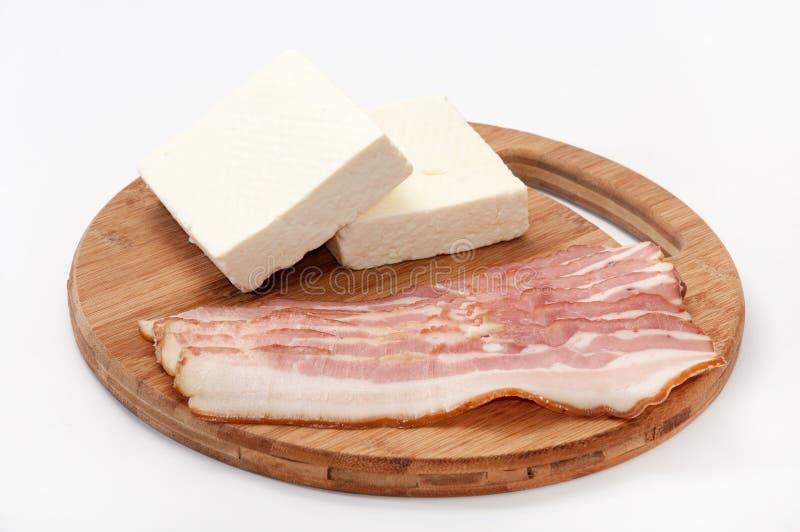 Las tiras de tocino arreglaron en un tablero de la cocina y un queso feta blanco foto de archivo