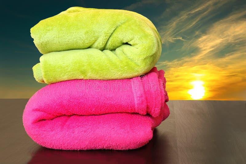Las toallas coloridas se prepararon para el baño de la puesta del sol en el mar fotos de archivo libres de regalías