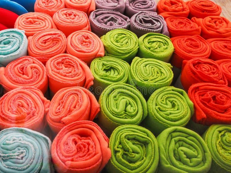 Las toallas multicoloras rodaron en una mentira del tubo en uno a en el estante La tela multicolora rodó en un tubo imagen de archivo libre de regalías