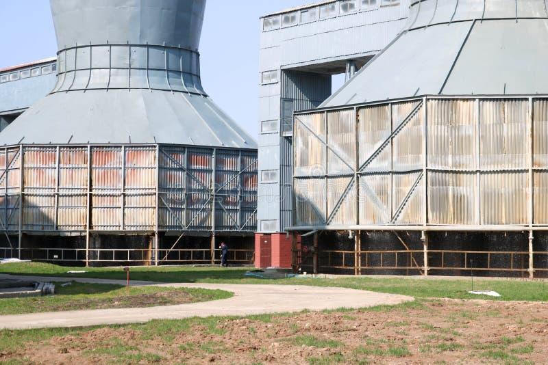 Las torres de enfriamiento grises grandes para el agua de enfriamiento están en fila, la energía, equipo en una refinería de petr foto de archivo