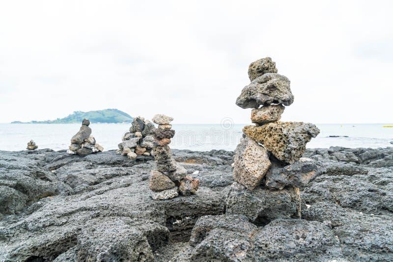 las torres de piedra en rocas basálticas en Hyeopjae varan, isla de Jeju imagenes de archivo