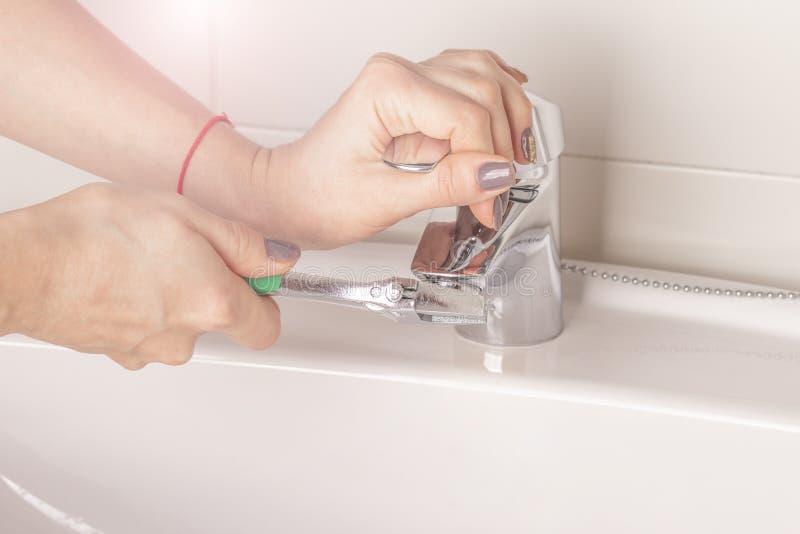 Las torsiones de la mano de la muchacha de torsiones el aerador del grifo en el cuarto de baño imagen de archivo