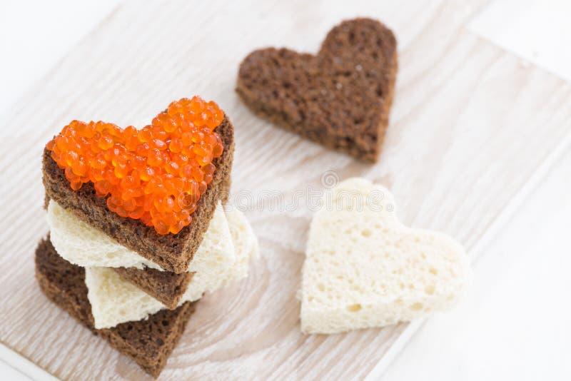 Las tostadas con el caviar rojo en corazón forman en el tablero de madera fotos de archivo libres de regalías