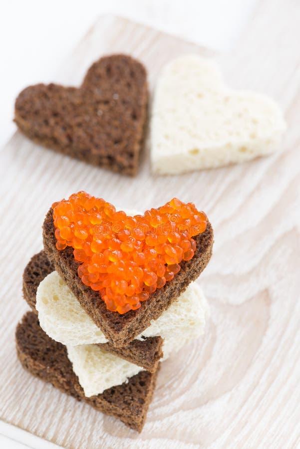Las tostadas con el caviar rojo en corazón forman en el tablero de madera, vertical foto de archivo libre de regalías