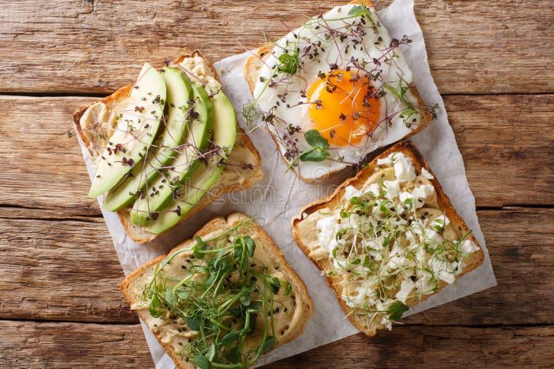 Las tostadas con el hummus, aguacate, queso feta, microgreen y primer del huevo visi?n superior horizontal fotografía de archivo libre de regalías