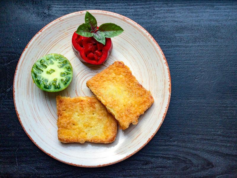 Las tostadas frieron en huevo con el tomate dulce verde fresco imagen de archivo libre de regalías