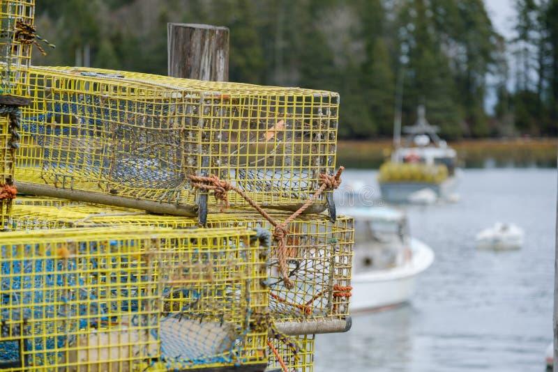 Las trampas coloridas de la langosta de Maine Lobsterman se sientan en un muelle que espera a fotografía de archivo