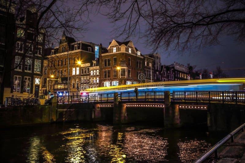 Las tranvías conducen por el puente viejo en la ciudad de Amsterdam en la noche foto de archivo libre de regalías