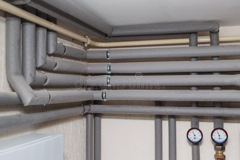 Las tuberías en los indicadores del aislamiento y de presión fluyen y vuelven los tubos en el cuarto de caldera de una casa priva imagen de archivo