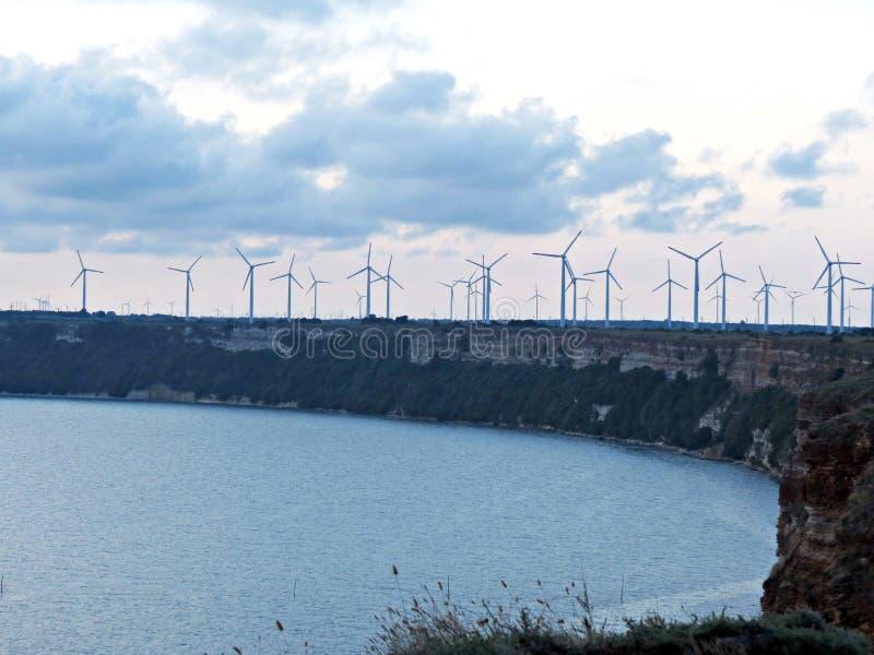 Las turbinas de viento se colocan a lo largo del banco de mar bajo crepúsculo foto de archivo libre de regalías