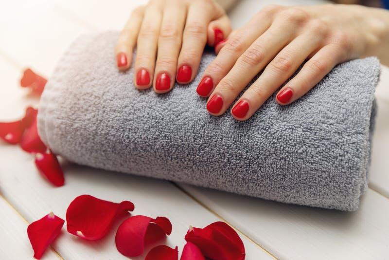 las uñas de la mujer con el esmalte de uñas rojo en la toalla ruedan imagen de archivo