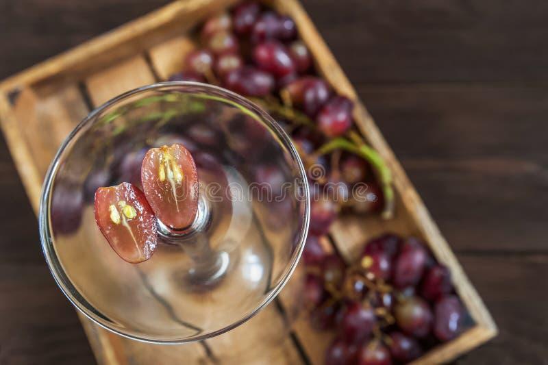 Las uvas cortaron por la mitad con los huesos en el fondo de un racimo de uvas azules en una caja de madera en una tabla oscura L fotos de archivo