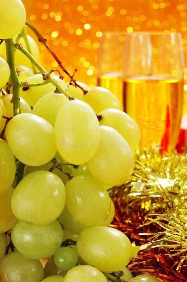 Las uvas españolas de la suerte y vidrios con champán imagenes de archivo