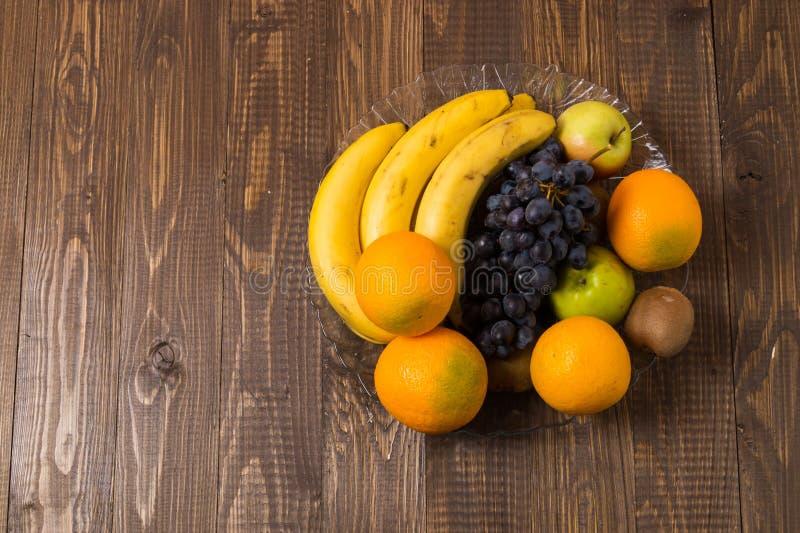 Las uvas, las naranjas, los plátanos, el kiwi y las manzanas están en plato fotos de archivo libres de regalías