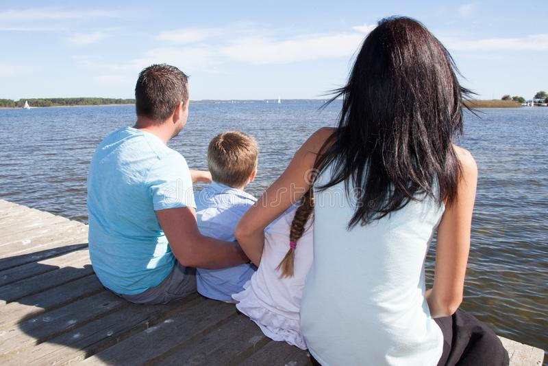 Las vacaciones de familia felices se sientan en la playa el pontón imagenes de archivo