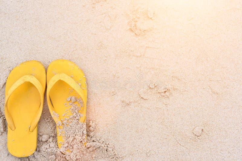 Las vacaciones de verano en las sandalias del amarillo de la playa en la playa tienen puesta del sol fotografía de archivo libre de regalías