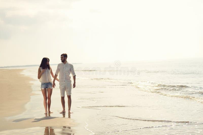 Las vacaciones felices de la playa de la diversión juntan caminar juntas riendo divirtiéndose en el destino del viaje fotografía de archivo libre de regalías