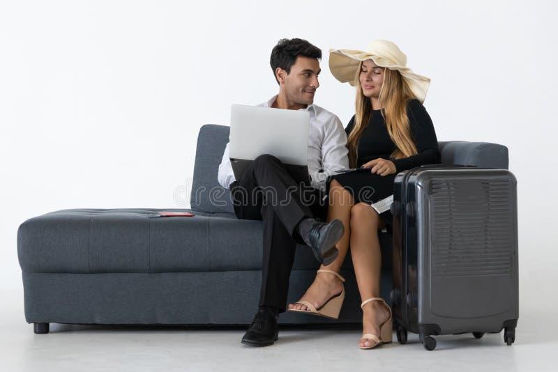 Las vacaciones que se sientan y de planificaciones de los pares felices atractivos disparan Concepto de las vacaciones de verano fotos de archivo