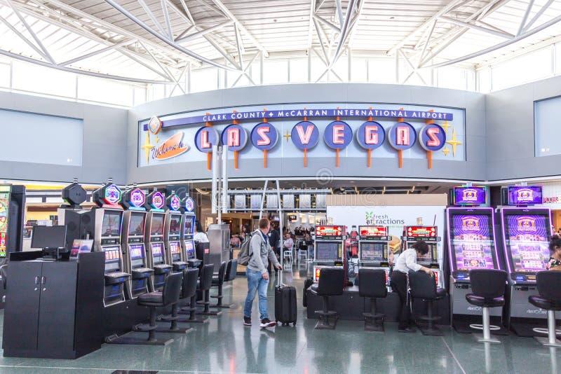 LAS VEGAS NEVADA, USA - 13 MAJ, 2019: Folk som spelar enarmade banditer på terminalen McCarran för internationell flygplats nedan royaltyfria bilder