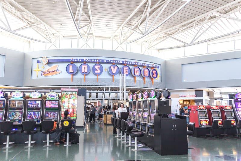LAS VEGAS NEVADA, USA - 13 MAJ, 2019: Folk som spelar enarmade banditer på terminalen McCarran för internationell flygplats nedan royaltyfri bild
