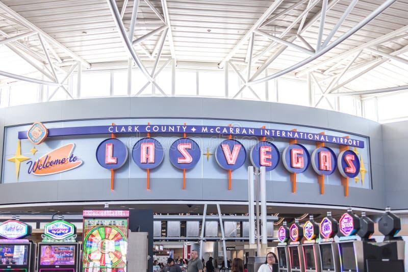 LAS VEGAS NEVADA, USA - 13 MAJ, 2019: Folk som spelar enarmade banditer på terminalen McCarran för internationell flygplats nedan arkivbilder