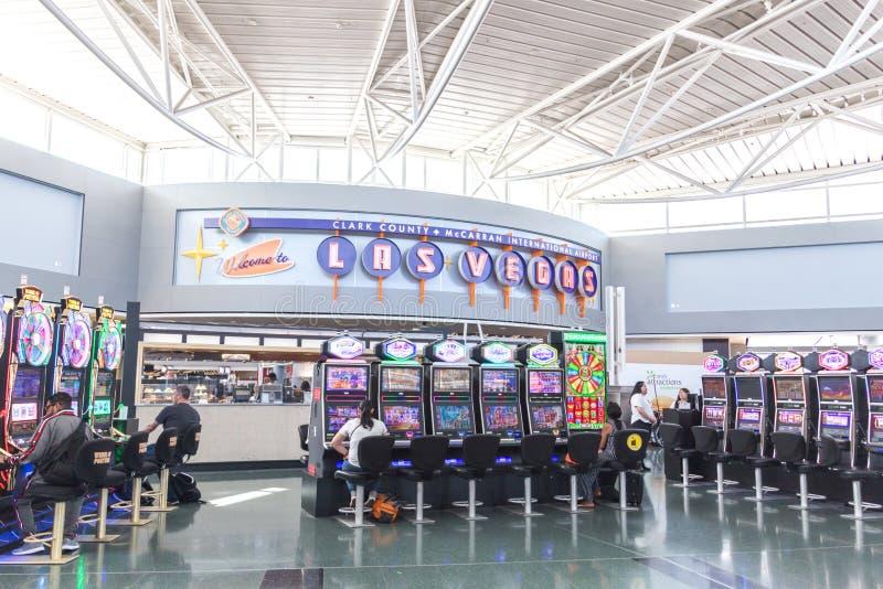 LAS VEGAS NEVADA, USA - 13 MAJ, 2019: Folk som spelar enarmade banditer på terminalen McCarran för internationell flygplats nedan royaltyfria foton