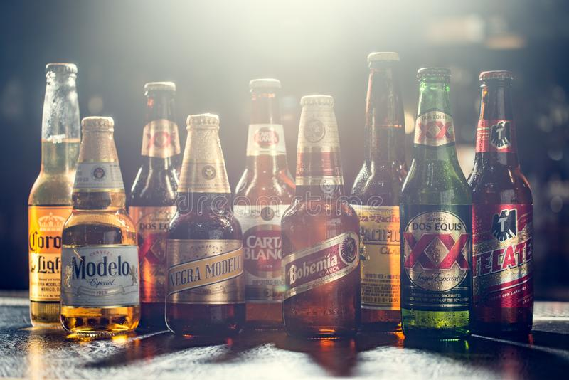 LAS VEGAS, NV - JULY 17, 2016: Popular Mexican Beers. Pacifico,. Corona, Bohemia, Tecate and Modelo beer bottles on a bar counter top with lens flare royalty free stock photo