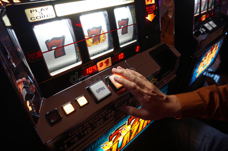 Las Vegas Slot Machine. A man plays a $1 US slot machine in Las Vegas royalty free stock photography