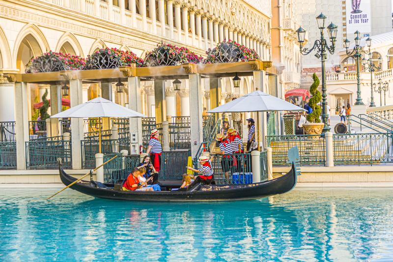 gondola with tourists at The Venetian Resort Hotel & Casino The resort opened  1999 with flutter of white doves, sounding trumpets stock photos