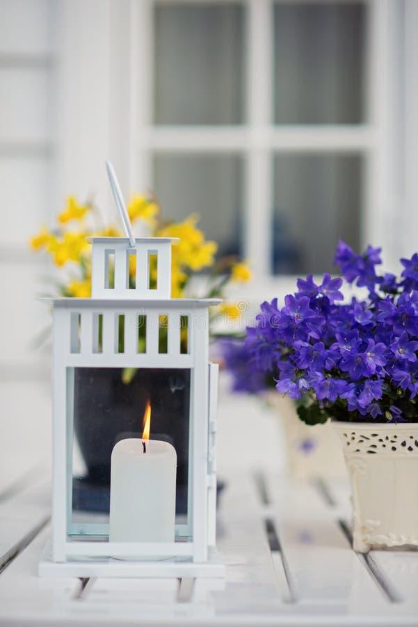 Las velas de la boda en la tabla de madera blanca y una púrpura florecen fotos de archivo