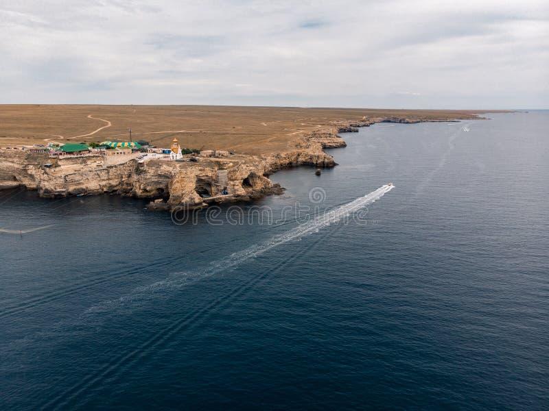 Las velas del barco en el mar cerca de las rocas en la Crimea fotografía de archivo
