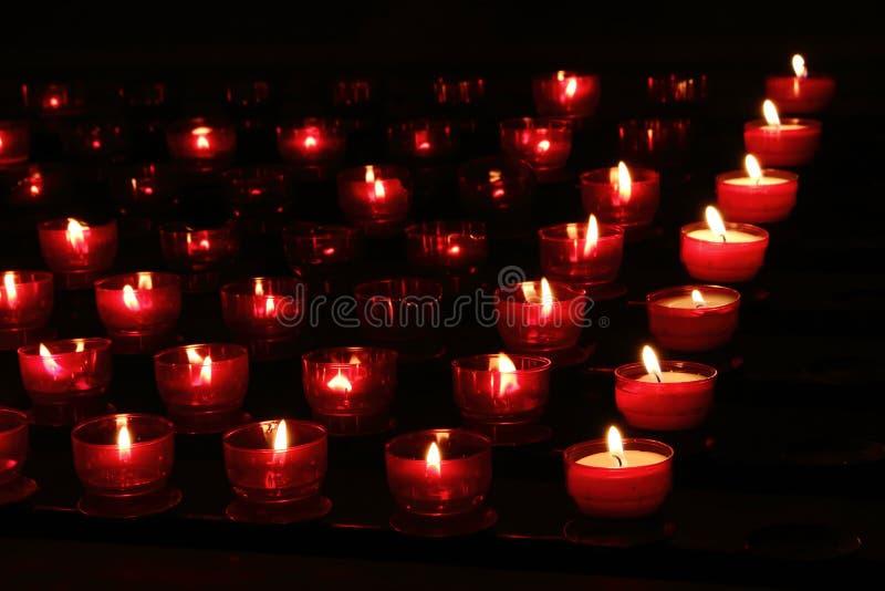 Las velas rojas con brillar intensamente se encienden en oscuridad en iglesia Fondo de la paz y de la esperanza Concepto de la re imagenes de archivo