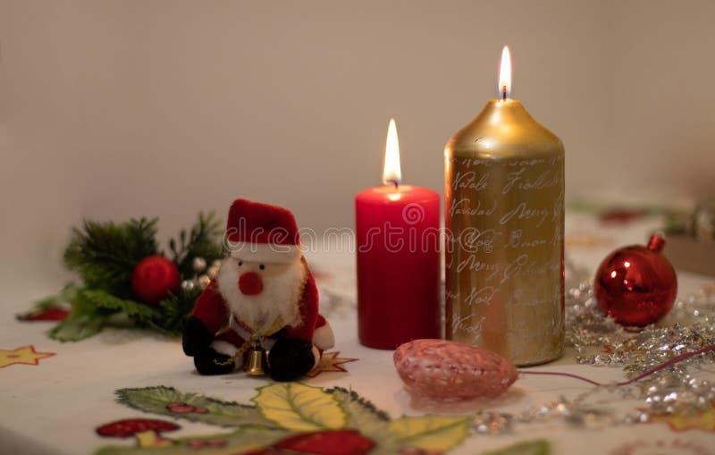 Las velas se encendieron con la decoración de la Navidad y una muñeca de Santa Claus en un mantel fotos de archivo libres de regalías