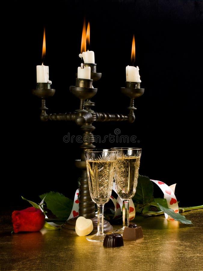 Las velas, vidrios con el vino, se levantaron imágenes de archivo libres de regalías